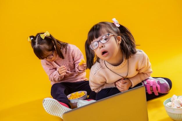 마시멜로와 칩. 그녀의 여동생이 뒤에 앉아서 그릇에서 먹는 동안 두 개의 꼬리를 가진 귀여운 소녀