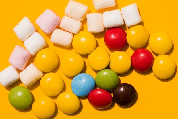 マシュマロと黄色の背景にカラフルなキャンディー