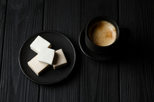 Marshmallow in a black plate on black wood table