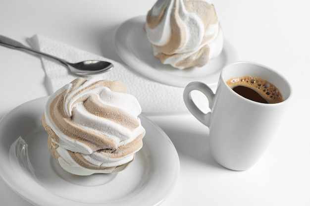 Marshmallow and coffee cup on white background