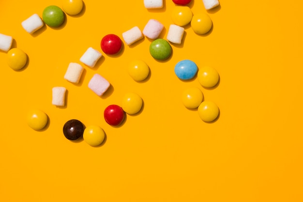 Marshmallow and colorful candies on yellow background