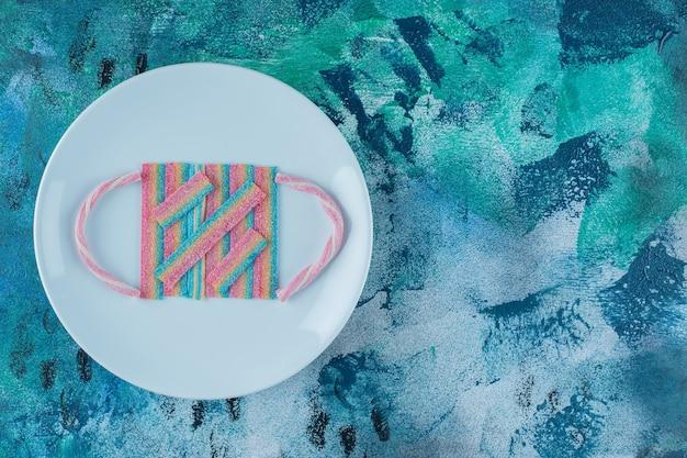 Marshmallow corde colorate arcobaleno intrecciate su un piatto, sul tavolo di marmo.