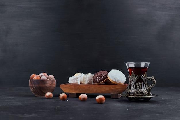 Зефирное печенье на деревянном блюде и стакан чая с орехами вокруг.