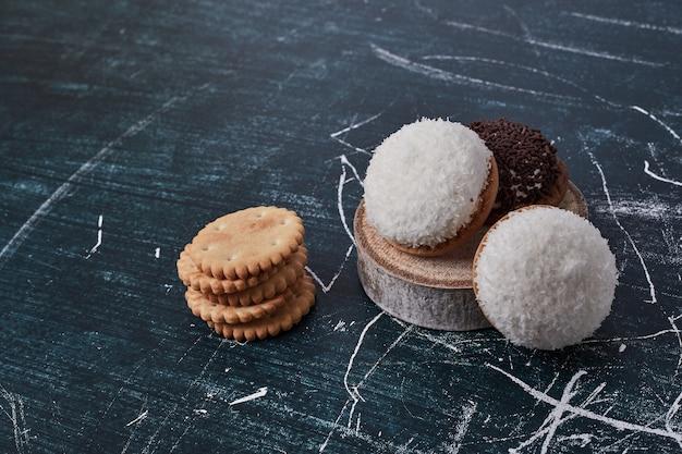 Biscotti marshmallow con cioccolato e polvere di cocco su un pezzo di legno.