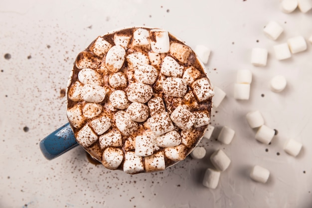 Marshmallow in a cup of hot chocolate or cocoa on a gray table.