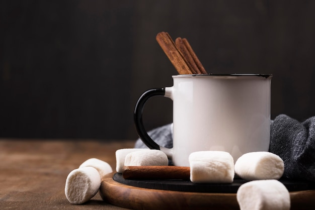 Marshmallow drink with cinnamon on wooden board