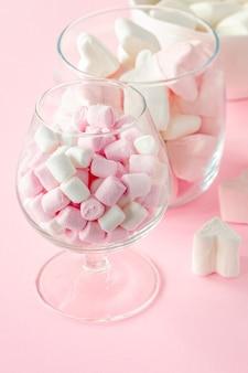 ピンクの背景に愛のコンセプトを持つマシュマロのハートの形とミニ。