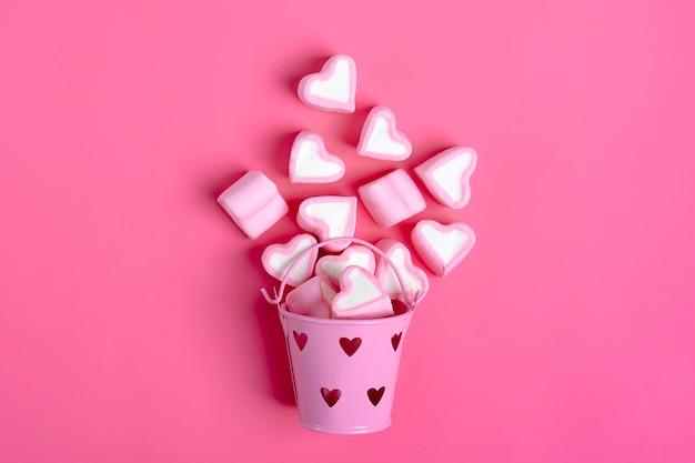 Marshmallow heart shaped spilled from bucket on pink background happy valentine's day