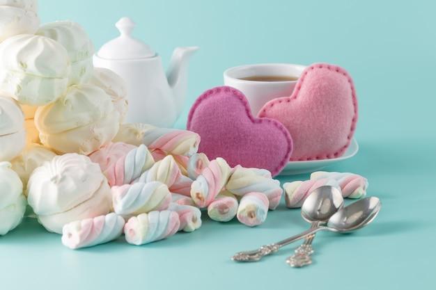 Зефир на аквамариновом фоне с чашкой чая и игрушечными сердечками