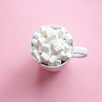 Marshmallow poured from a white mug on a pastel pink