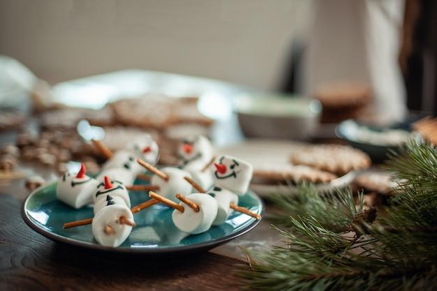マシュマロの雪だるまは皿の上に横たわっています。クリスマスの準備。ココアの装飾。