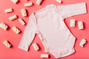 Marshmallow surrounded with pink baby onesie on peach background