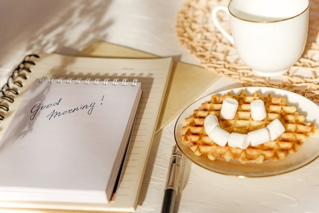 Marshmallow waffle smile greeting card good morning on white textured table. flat composition.