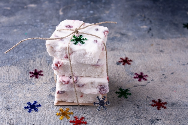 Marshmallow with berries tied with twine and confetti snowflakes