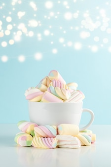 Marshmallows colorful chewy candy in a cup on blue bokeh wall