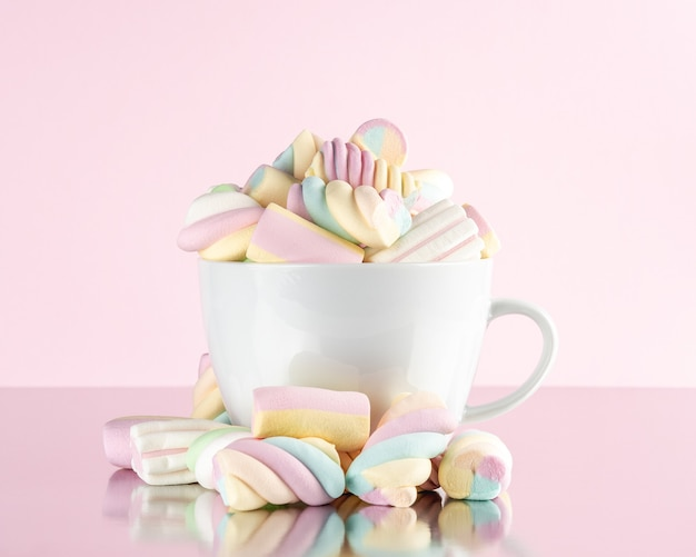 Marshmallows colorful chewy candy in a cup on pink background