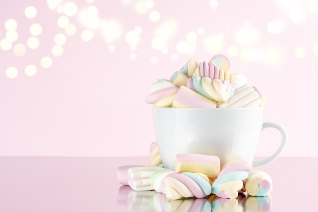 Marshmallows colorful chewy candy in a cup on pink bokeh background