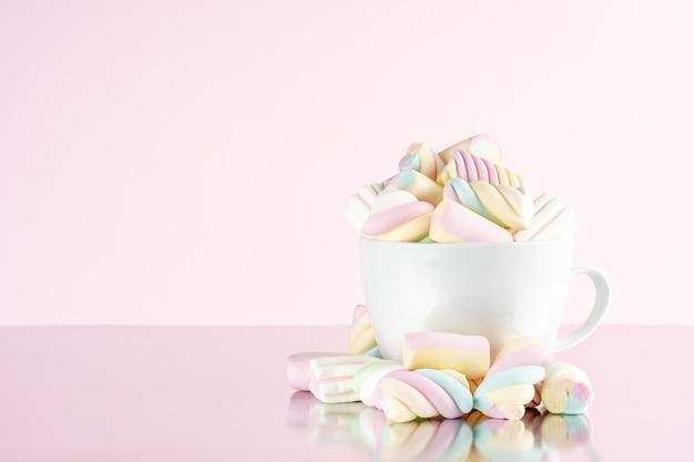 Зефир красочные жевательные конфеты в чашке на розовом фоне