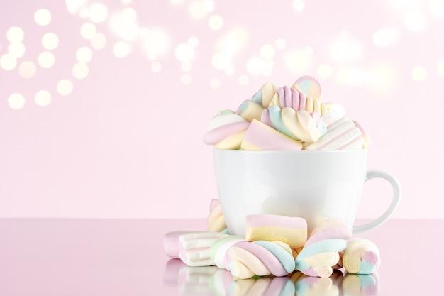 분홍색 bokeh 배경에 컵에 마시맬로 다채로운 질긴 사탕