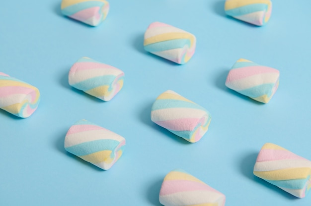 マシュマロは、青のパステルカラーの背景にカラフルなパターンで、広告用のコピースペースがあります。食品の背景、フラットレイミニマルな構成