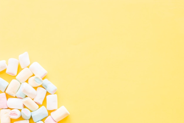 Marshmallows on the corner of the yellow background