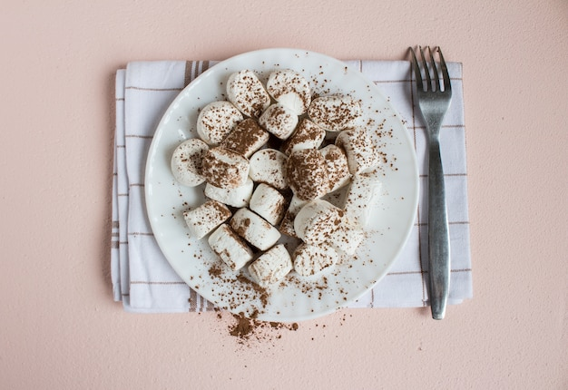Marshmallows dusted with cocoa on white plate with fork on towel. sweet food top view