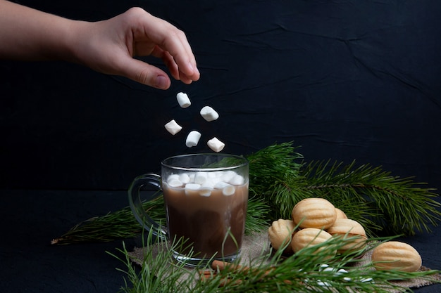 Marshmallows falls from hand in glass mug with hot chocolate cocoa drink. copy space. winter food and drink concept. christmas and new year.