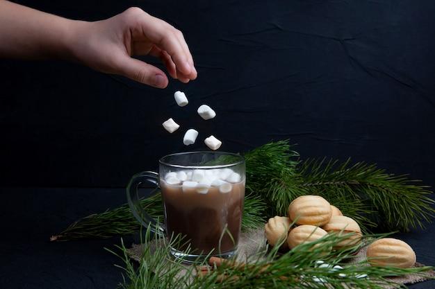 マシュマロは、ホットチョコレートココアドリンクと一緒にガラスのマグカップに手から落ちます。スペースをコピーします。冬の食べ物や飲み物のコンセプト。クリスマスと新年。