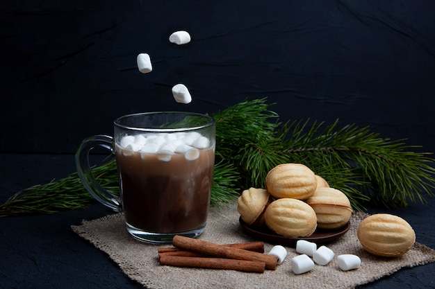 マシュマロは、ホットチョコレートココアドリンクと一緒にガラスのマグカップに落ちます。冬の食べ物や飲み物のコンセプト。フライングマシュマロ。