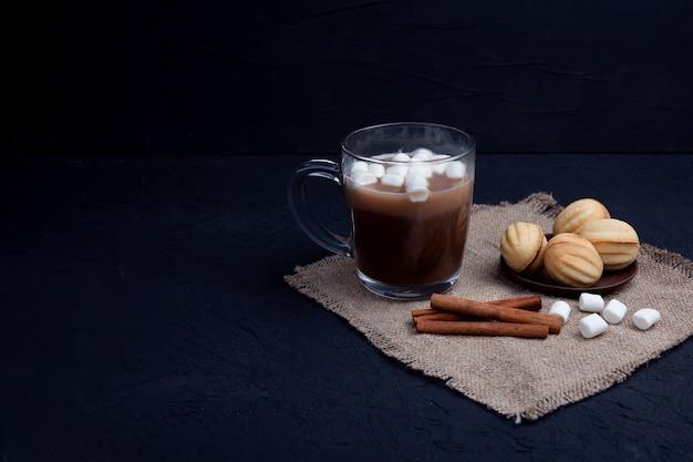 マシュマロは、ホットチョコレートココアドリンクと一緒にガラスのマグカップに落ちます。冬の食べ物や飲み物のコンセプト。