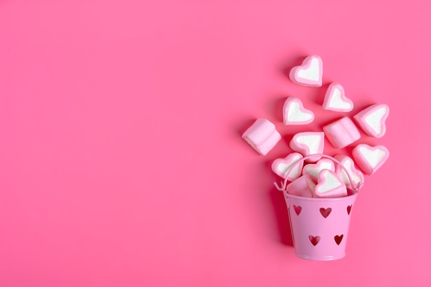 Marshmallows heart shaped spilled from pink iron bucketon pink background happy valentine's day