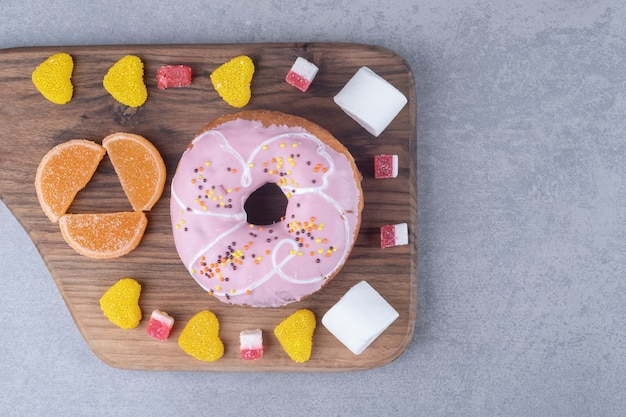 Зефир, мармелад и пончик на деревянной доске на мраморной поверхности