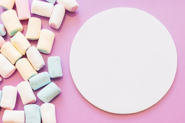 Marshmallows near the blank circular frame on pink backdrop