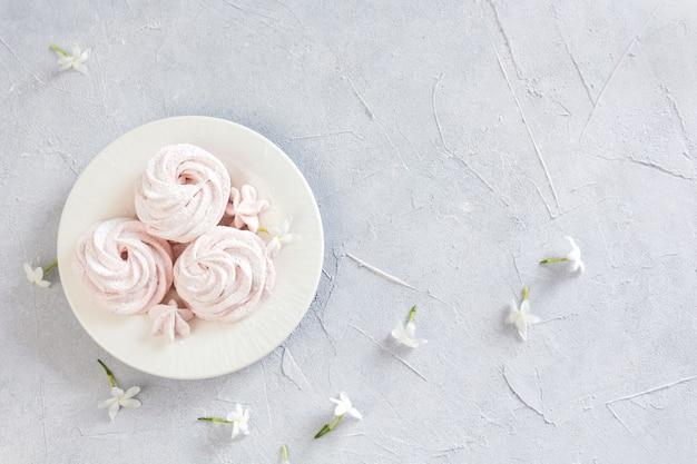 Зефир на тарелке, украшенной цветами на белом текстурированном фоне, вид сверху