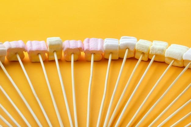 텍스트를 위한 공간이 있는 노란색 배경 위에 막대기에 있는 마시멜로