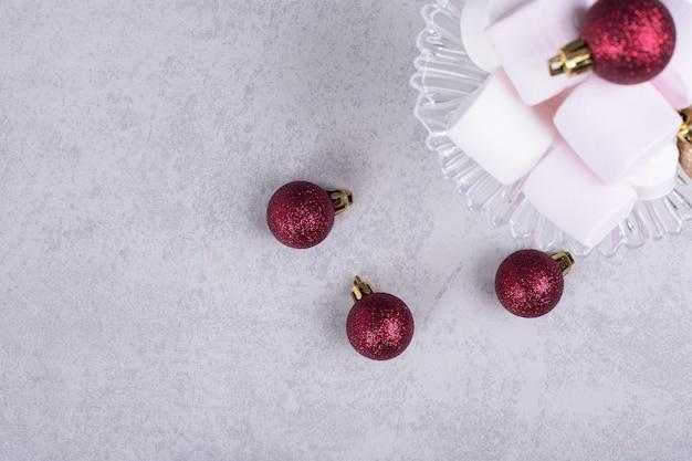 クリスマスボールとガラスプレート上のマシュマロ。高品質の写真