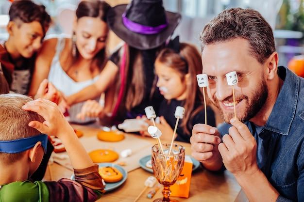 スティック上のマシュマロ。妻と子供たちとハロウィーンを祝っている間棒でマシュマロを保持しているひげを生やした父の笑顔
