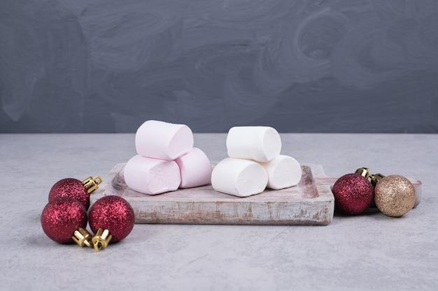 クリスマスボールと木の板のマシュマロ。高品質の写真