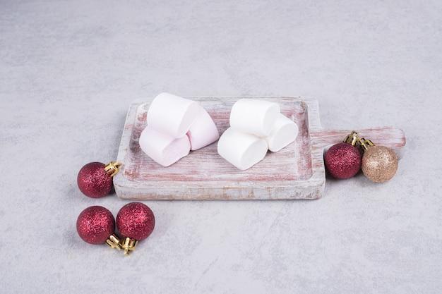 Зефир на деревянной доске с елочными шарами. фото высокого качества