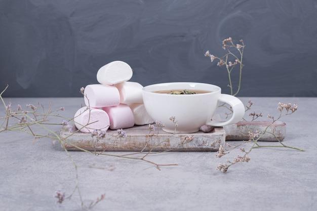 Зефир на деревянной доске с чашкой чая. фото высокого качества