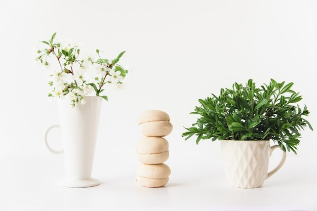 Marshmallows stack, white flowers in a white vase and greens in a white cup on white background
