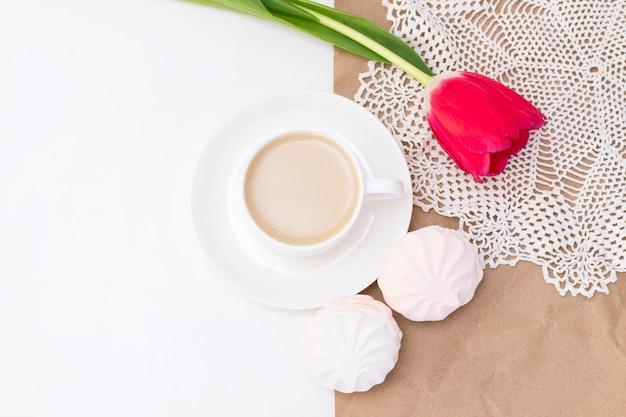 Marshmallows, tea or coffee with milk and a tulip flower. on a light surface. romantic spring morning. delicate breakfast, breakfast in bed. for the beloved. surprise.