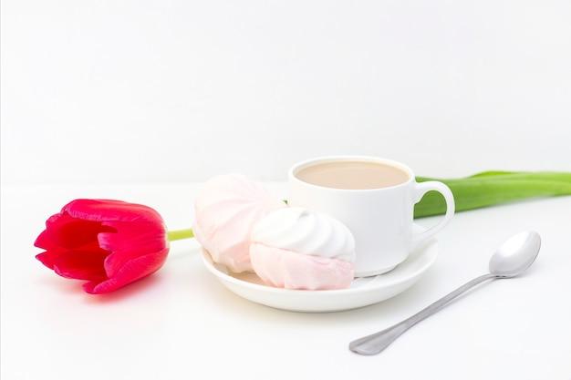マシュマロ、紅茶またはコーヒーとミルクとチューリップの花。明るい表面にロマンチックな春の朝。繊細な朝食、ベッドでの朝食。最愛の人のために。驚き。