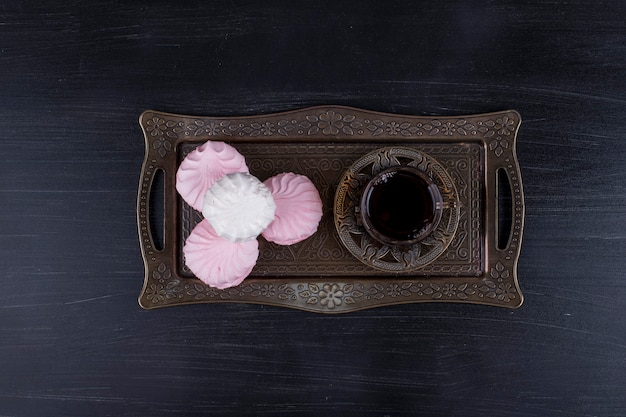 金属製の大皿、上面にお茶のグラスとマシュマロ
