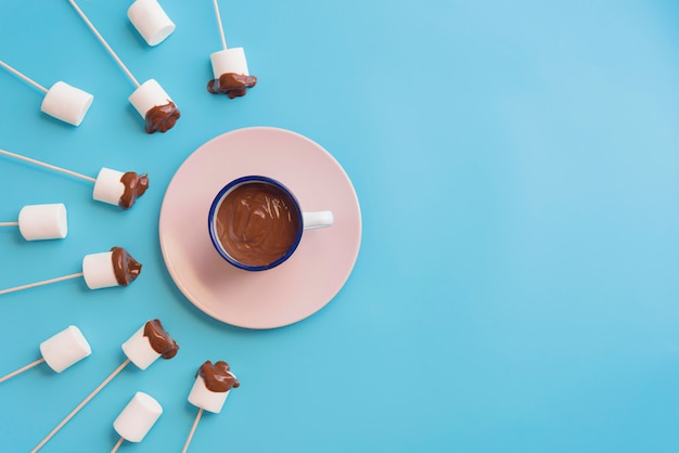 Marshmallows with chocolate in a blue background