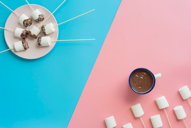 Marshmallows with chocolate in a blue and pink background