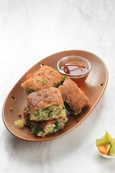 Martabak telur - популярная уличная еда в индонезии. яйцо, зеленый лук в тонком мучном кляре