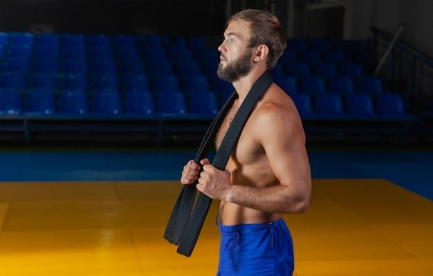 Мастер единоборств с голым торсом и черным поясом в спортивном зале