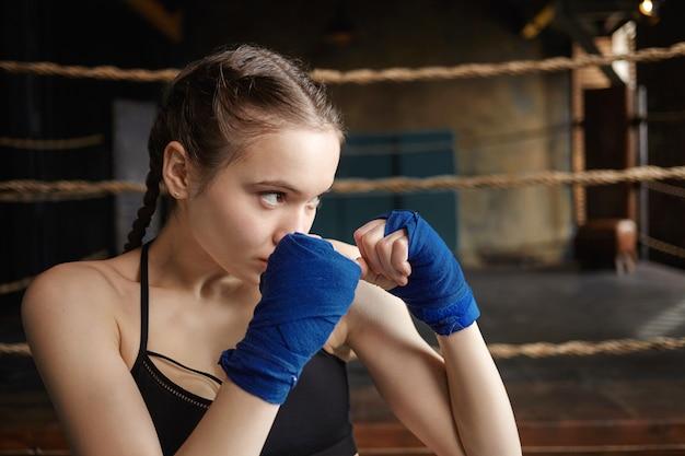武道、ボクシング、キックボクシング、トレーニングのコンセプト。ハンドラップを身に着けて、屋内で運動する美しい10代の少女の肖像画をクローズアップ