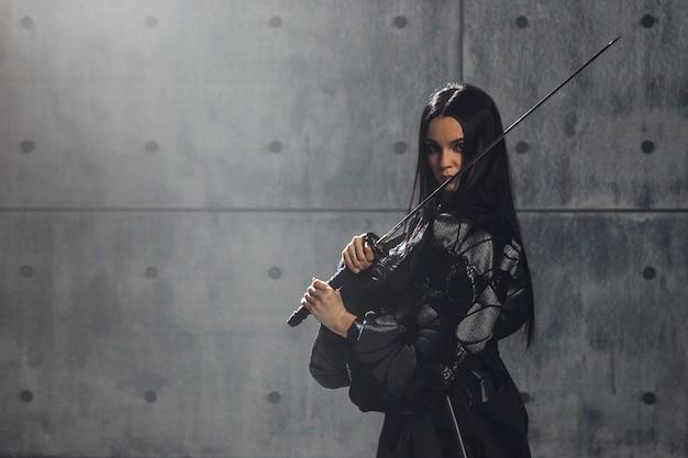 武道の概念。刀でポーズをとる着物の女性